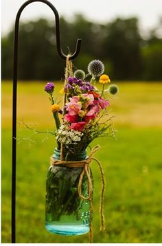 shepards hook with mason jars hanging surrounded with lace and a candle inside