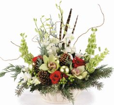 WINTER ABUNDANCE:  A white ceramic container overflowing with exquisite green cymbidium orchids, red roses, green Christmas balls, pinecones, berries & evergreens.   #MatlackFlorist