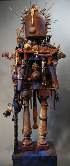 """The Warrior, 2005-12, (50"""" H x 21 1/2""""W 14"""" D)    Mixed media; including wood, seed beads, wood beads, silver beads, ceramic beads, coins, leather, handmade nails, antique hat form, wooden box, bones, bees wax, cast iron, tin, silver, clay, American buffalo horn, magnolia seed pod, hammer handle, carved wood figures, table legs, bells, net floats,African hand forged arrow points, cotton, paint, etc."""