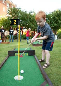 A St. Jude patient gets a hole in one on the mini golf course set up on the Target House lawn!