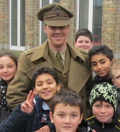 Filming for Parade's End -Ahhh, just when he can't get any cuter, he goes and poses with a bunch of kids.