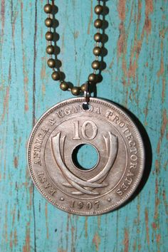 Vintage Antique Coin East Africa Uganda Necklace with Crossed Elephant Tusk (Hole in the Middle). $9.99, via Etsy.