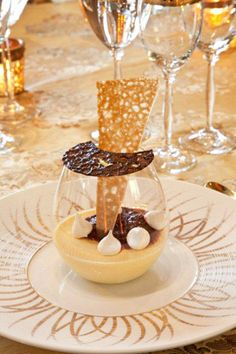 Passion fruit panna cotta garnished with malted milk meringues, topped with a chocolate cookie...