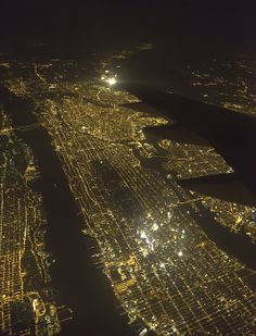 Thousands of lights of Manhattan Island at night, with Hudson River (left) n East River (right) n wing of commercial jetliner, New York City.