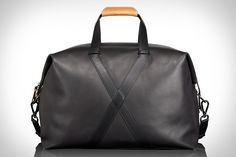 "TUMI BASHFORD DUFFEL BAG - An all-black bridle leather exterior accented by a natural leather handstrap, this roomy overnight bag features an ""X"" pattern on the sides that sets it apart from its traditional contemporaries. Other features include a detachable shoulder strap, contrasting beige interior lining, and several interior pockets for organizing smaller items."
