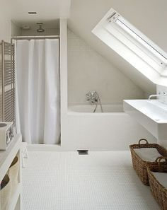 Wonderfully simple white loft bathroom. Love the built in shower and bath, and the way they all fit beautifully under the sloping ceiling.