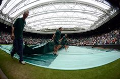 Grounds crew members pull the cover over Centre Court during a rain delay. - Matthias Hangst/AELTC
