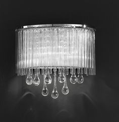 FL2161/2 Spirit single wall light chrome and crystal glass. Chrome finish fitting with small crystal drops inside a Lurex fabric shade. Delicate glass rods surround the shade and teardrop shaped smooth glass drops hang beneth. Supplied with G9 mains voltage halogen bulbs which are suitable for dimming. 2 x 33w G9 Lamps included Height- 27cm Width- 30cm Projection - 16cm BRAND: Franklite REFERENCE- FL2161/2 AVAILABILITY: 3-4 Working Days