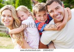 Portrait Of Happy Family In Garden - Shutterstock Premier