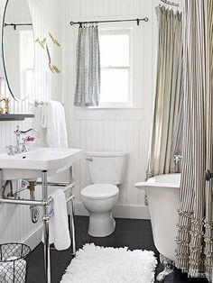 Neutral bathroom color schemes never go out of style, and black and white is a classic. Beaded board laid vertically and deep crimson flooring visually heighten this small but stylish bath. Shiny finishes, including a curvaceous faucet, metal vanity legs, and silver tub feet, add interest./