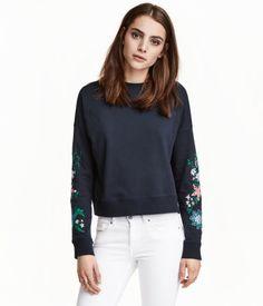 Mørk blå. En lett sweatshirt med trykk. Den er noe kortere og videre i modellen. Lange ermer og vrangbord rundt halsringningen, nederst og på ermene.