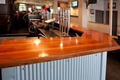 Turks Bar.  Solid timber joinery bar counter with micro corrugated iron cladding, stainless steel bar service counter with integrated draught beer and post mix services.