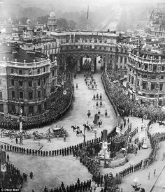 Pomp: Crowds line the streets as the carriage carrying King George VI on coronation day through Admiralty Arch in central London - 1937