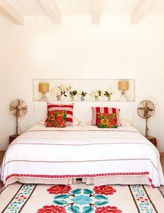 white walls  + ceiling beams + pops of color + retro fans + floral rug + white duvet #homedecor