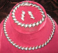 Demi Parure of Earrings, Bracelet and Necklace by Milor de San Marco. Three pieces of high fashion jewelry made up of sterling silver half-circle links that resemble elbow macaroni. Earrings (pierced): 3/4 x 1/3 inch. Bracelet: 7 x 1/3 inch. Necklace: 10 x 1/3 inch