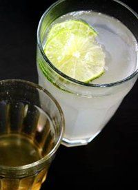 Ginger Syrup Soda: 1/2 pound fresh ginger root - about 1 1/2 cups peeled and chopped.. 2 cups water.. 3/4 cup sugar.. 1 teaspoon whole cloves (optional).. 1 cinnamon stick (optional).. Sparkling water.. Lime wedges..