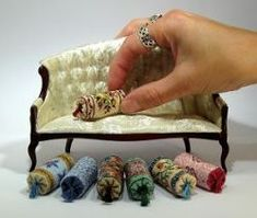 These are so cool...tiny needlepoint bolsters with tassels for doll house.