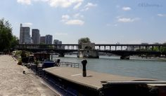 A photo taken from the bank of the River Seine you can see the Pont de Bir-Hakeim bridge in Paris, showing the two tier bridge which has a Metro going over the top with a road and foot path beneath it, as well as many houseboats along the river's edge.  You may also like http://www.eutouring.com/images_pont_de_bir-hakeim.html