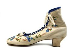 Lady's canvas pumps with very high back lacing through seven metal eyelets. Decorated with embroidery. Low knock on heel, France, circa 1860-1865.