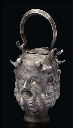 Roman silver Janus Silenus head balsamarium, 2nd-3rd century A.D. With partial gilding, 11 cm high including handle. Private collection