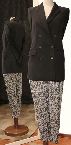 Giacca Pierre Balmain chiusura doppiopetto in fresco di lana nero. Pantaloni tuta di seta a fiori grigi. Per info: petitnoir-vintage.it