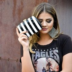 Blogger Thássia Naves with a gorgeous striped Serpui clutch