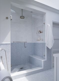 Walk-in shower with built-in seat, white and light blue tile, built in shelves for shampoo, and rain shower head.