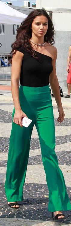 Who made Adriana Lima's green pants, sandals, and black one shoulder top?