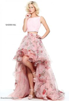 Sherri Hill 51098 is a 2-piece prom dress with a high neckline, low back crop top and a floral printed organza skirt with a high low hem.