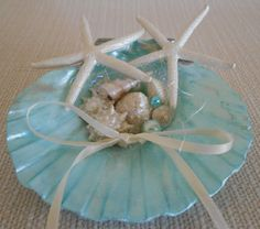 Beach Wedding Ring Bearer. This beautiful Ring Bearers Shell would make the perfect addition to your Beach Wedding.  A gorgeous scallop shell has been used as a base and additional shells, starfish and pearls have been added together with iridescent threads and ribbon to create this stunning Ring Bearers Shell.  The pictures show the Shell in Aqua/Turquoise/Mother of Pearl but they can also be made in Mother of Pearl with Light Pink/Pink, Mother of Pearl with Lilac, Mother of Pearl with Mint…