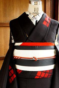 黒地に、黄色と赤と白の格子の四角模様がポンポンとリズミカルに織り出されたレトロモダンな単着物です。
