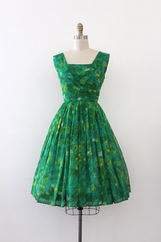 Beautiful green floral chiffon evening dress from the late 1950s. This dress features a fitted waistline and bodice with an open skirt.