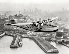 """July 22, 1936. """"Aerial view of Pan American Airways 'China Clipper' (Martin M130 Flying Boat) over San Francisco with Coit Memorial Tower at left. Clyde H. Sunderland, commercial and aerial photographs, Oakland, Calif."""""""