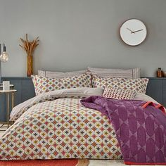 Otto features a graphic circle print in vibrant shades of magenta, spicy tangerine and warm ochre with subtle accents of charcoal, inspired by a traditional Scandinavian pattern.