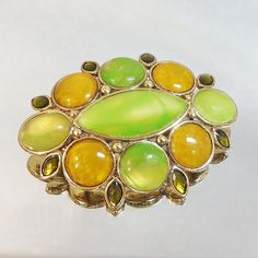 This #vintage Liz Claiborne brooch is just beautiful!  It features a gold tone oval shaped brooch with green and gold marbled cabochons.   Rolling C-clasp on both the heart ... #ecochic #etsy #jewelry #jewellery #holiday2014etfs