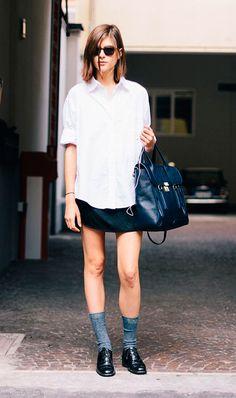 Street style look com camisa branca, saia preta, sapato preto masculino e meia cinza aparente.