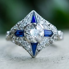 Art Deco 1920's Diamond Engagement Ring w/ Sapphire Accents Platinum. This amazing Art Deco engagement ring dates from the 1920's and is centered with a 1.41 carat Old European cut diamond grading H / VS2. Accenting the center diamond are four natural sapphires and 22 diamonds set into a pierced plaque atop sculpted shoulders. This ring is crafted of solid platinum and is in very good condition.