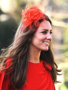 kate in red with a brightly-colored fascinator and matching dress