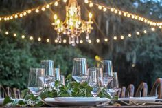 Our Cafe Lights and Chandelier hanging above a dining table! The cafe lights provide a warm glow, perfect to set a romantic mood and also great for photographers!  #weddingdecor #cafelights #chandeliers #wineglasses #outdoorwedding #legarewaringhouse #Charleston #southcarolina #lowcountry #wedding