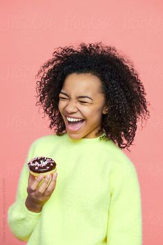 Portrait of pretty black girl with afro hairstyle wearing rich yellow sweater holding chocolate glazed donut and laughing joyfully on pinkish orange background