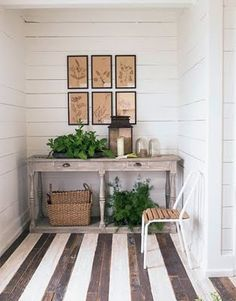 Understated entry way made special by all the details. The painted stripes on the hardwood floor, faded pressed plants on the wall and ferns for some color.