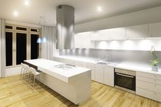 A modern kitchen in white with under the cabinet lighting, an eat-in bar, and bamboo flooring, in addition to a massive cylindrical vent hood and pendant lights. A single orchid adds a bit of organic flavor.