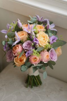Bouquet in peach and lilac with vuvuzela, ocean song and peach avalanche roses, eustoma, clematis, alchemilla and eucalyptus. Liberty Blooms