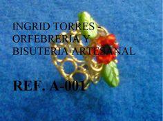 anillo elaborado con alambre de gold field, cristalitos rojos y negro, hojas de jade..
