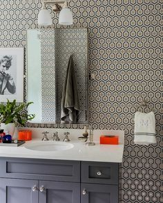 Contemporary gray bathroom boasts a wall clad in Hicks Hexagon Wallpaper lined with a charcoal gray vanity topped with white quartz and a rectangular pivot mirror lit by a 2 light sconce.