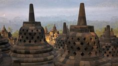 Borobudur - 9th-century Mahayana Buddhist Temple in Magelang, Central Java, Indonesia. The monument consists of six square platforms topped by three circular platforms, and is decorated with 2,672 relief panels and 504 Buddha statues. A main dome, located at the center of the top platform, is surrounded by 72 Buddha statues seated inside a perforated stupa.