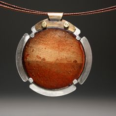 "Nissa Kubly, 'Farm Horizaon (double pinhole photo), Wisconsin' Necklace in copper, vitreous enamel, sterling silver, brass, and stainless steel neckwire. Pendant measures 1.5"" in diameter."