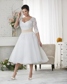 1523 Unforgettable by Bonny Bridal - Organza tea length, plus size wedding gown with sheer lace sleeves.