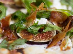 Fig, Goat Cheese and Prosciutto Flatbread is smothered in Ricotta and Goat Cheese, covered with fresh Black Mission Figs, Arugula and Prosciutto, then drizzled with Extra Virgin Olive Oil and a Port Reduction.
