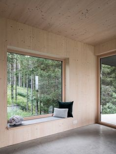 In the living room, a large window frames views of the pine forest in the north. Tagged: Living Room and Concrete Floor. Photo 13 of 17 in A Silvery Gabled Home Cantilevers Out Amid the Austrian Alps. Danish Architecture, Mini Chalet, Retreat House, Modern Mountain Home, Forest House, Good House, Common Area, Large Windows, Concrete Floors